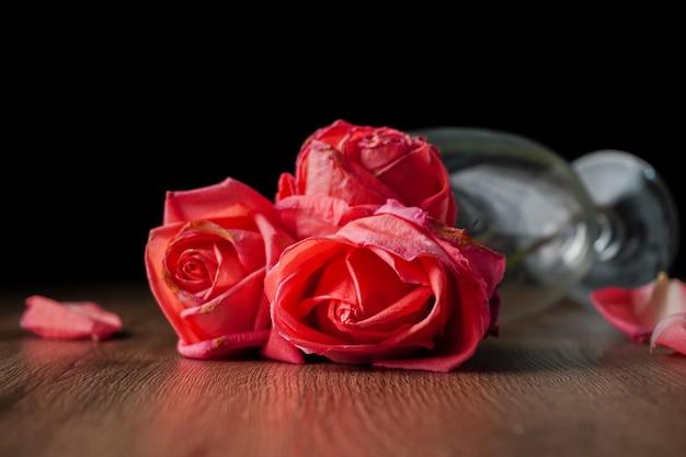 Grupa różowych róż umieszczonych w kieliszku szampana, które spadają na drewniany stół w ciemnym kolorze