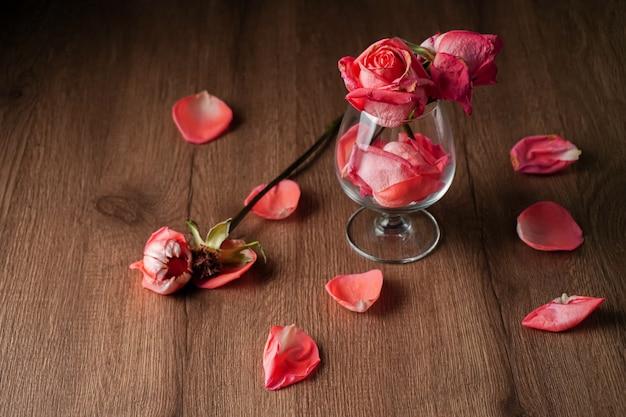 Grupa różowych róż umieszczonych w kieliszku wina, które spadają na drewniany stół w ciemnym kolorze