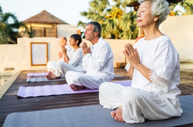 Grupa seniorów ćwiczących rano jogę
