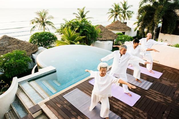 Grupa seniorów praktykujących jogę rano