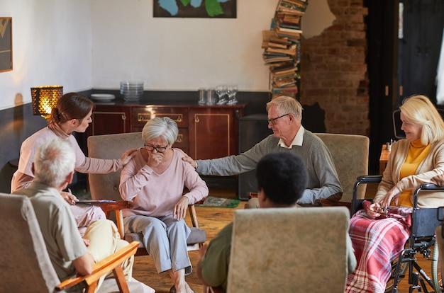 Grupa seniorów siedzących w kręgu podczas sesji terapeutycznej w domu starców, skupiająca się na płaczu kobiety, kopiująca przestrzeń