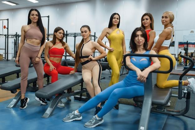 Grupa sexy kobiet pozuje na maszynie do ćwiczeń w siłowni, widok z przodu.