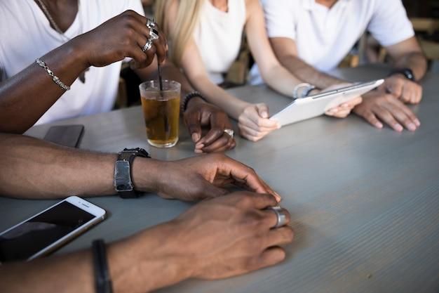Grupa siedzi na stole z bliska tabletu