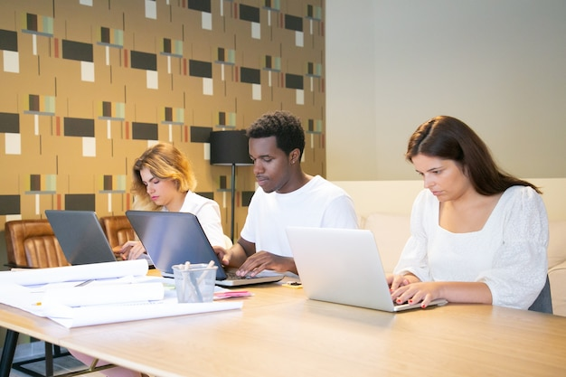 Grupa skupionych projektantów siedzi razem przy stole z planami i pracuje nad projektem