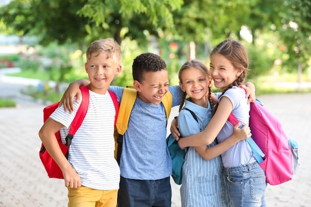 Grupa ślicznych małych uczniów na zewnątrz