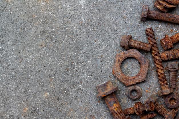 Grupa śmieciarskie stare ośniedziałe stalowe dokrętki i rygle wypiętrzają na zakurzonej cementowej podłoga z selekcyjną ostrością i kopii przestrzenią. tło do koncepcji mechanicznej lub recyklingu i ponownego wykorzystania