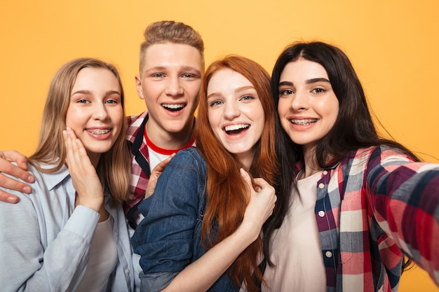 Grupa śmiejących się przyjaciół szkoły biorąc selfie