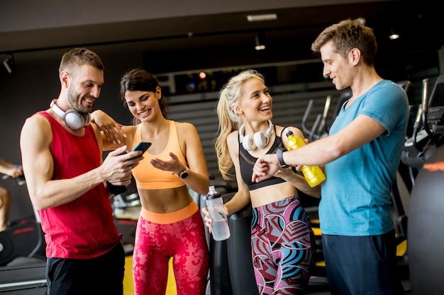 Grupa sportowa młodych ludzi na siłowni