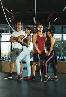Grupa sportowców mięśni robi trening na siłowni. gimnastyka, trening, elastyczność treningu fitness. aktywny i zdrowy tryb życia, młodość, kulturystyka. pozuje, wygląda pewnie i fajnie. praca zespołowa.