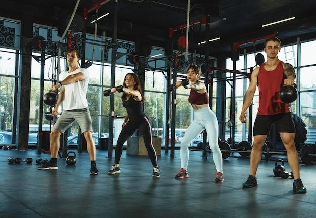 Grupa sportowców mięśni robi trening na siłowni. gimnastyka, trening, elastyczność treningu fitness. aktywny i zdrowy tryb życia, młodość, kulturystyka. trening z ciężarami, robienie przysiadów.