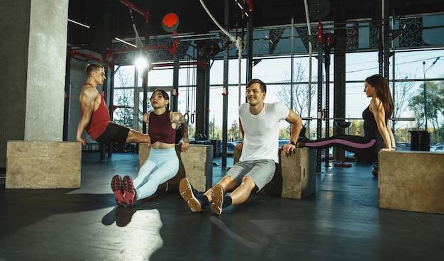 Grupa sportowców mięśni robi trening na siłowni. gimnastyka, trening, elastyczność treningu fitness. aktywny i zdrowy tryb życia, młodość, kulturystyka. trening ze sportowymi boksami do skoków.