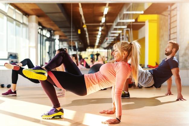 Grupa sportowców o zdrowych nawykach wykonujących ćwiczenia siłowe na podłodze siłowni. w lustrze w tle.