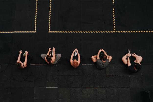 Grupa sportowców rozciągająca się razem, aby rozpocząć rutynowe ćwiczenia crossfit.