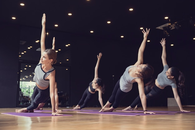 Grupa sportowej rasy mieszanej rasy białej i azjatyckiej, zarówno kobiet, jak i mężczyzn uprawiających jogę, pozuje w siłowni studio, joga i fitness opracowuje koncepcję opieki zdrowotnej