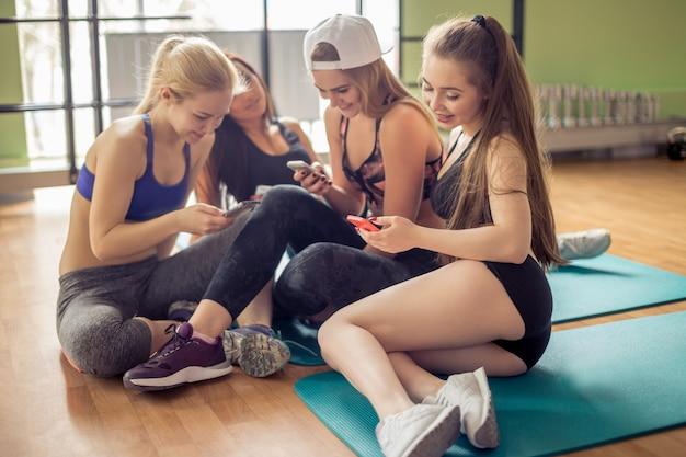 Grupa sporty żeńscy przyjaciele używa smartphone przy gym.