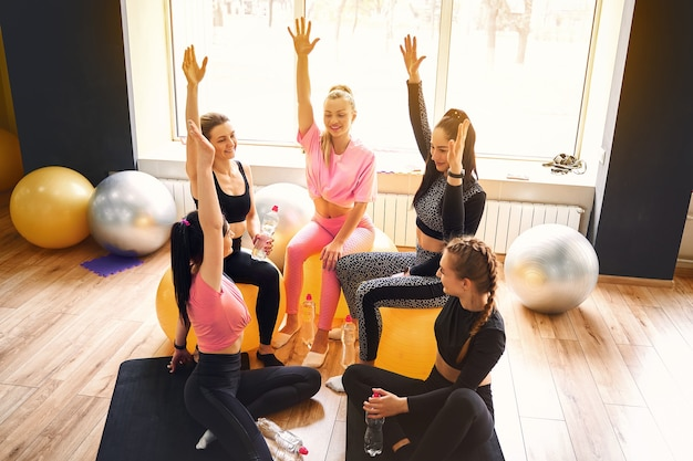 Grupa sprawnych szczęśliwych ludzi dając piątkę w sali fitness studio rozmawiając w kręgu po szkoleniu seminaryjnym