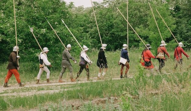 Grupa średniowiecznych rycerzy tocząca bitwę. wojownicy idący z włóczniami, mieczami, łukami i hełmami na głowach. rekonstrukcja historyczna z xiv-xv wieku, flandria.