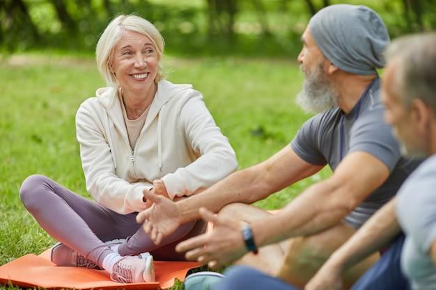 Grupa starszych mężczyzn i kobiet noszących stroje sportowe siedzi na matach w parku, rozmawiając o czymś podczas przerwy