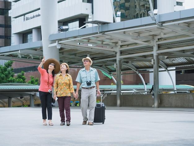 Grupa starszych podróżuje po mieście, starszy mężczyzna i starsza kobieta rozglądają się i spacerują po mieście