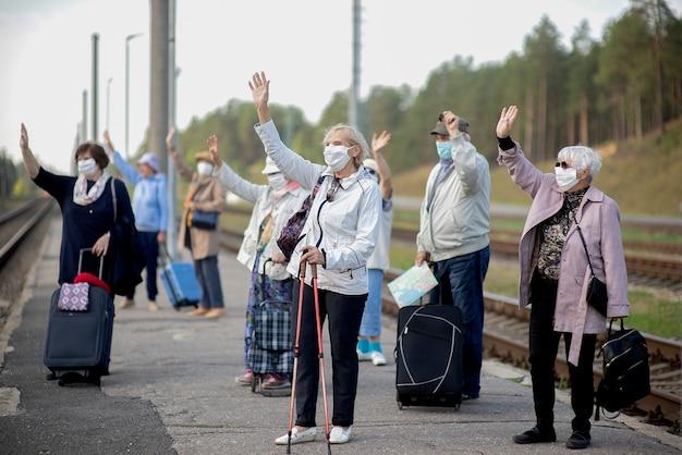 Grupa starszych seniorów z maskami na twarz czeka pociągiem przed podróżą