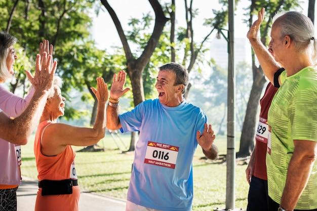 Grupa starszych sportowców dając piątkę