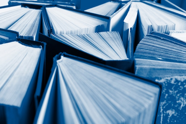 Grupa starych książek w twardej oprawie zabarwione w klasyczny niebieski kolor, widok z góry