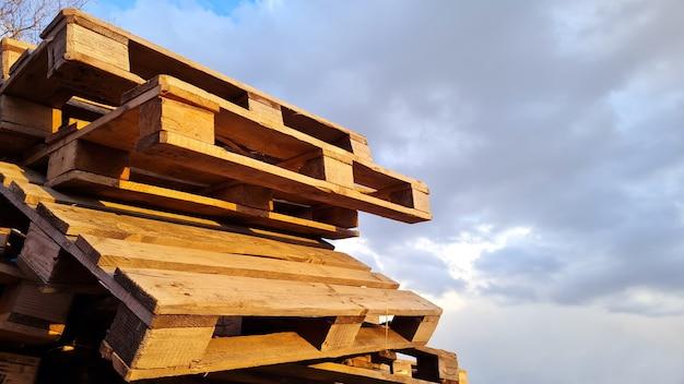 Grupa starych używanych palet drewnianych jest stos na zewnątrz w magazynie przedsiębiorstwa dostarczającego ładunki na pochmurnym niebie w tle kopii przestrzeni