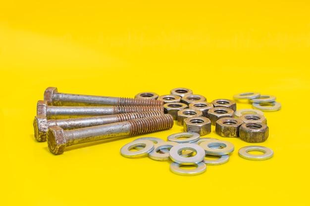 Grupa starych zardzewiałych śrub, podkładek i nakrętek na żółtym tle elementy mocujące. zdjęcie stockowe
