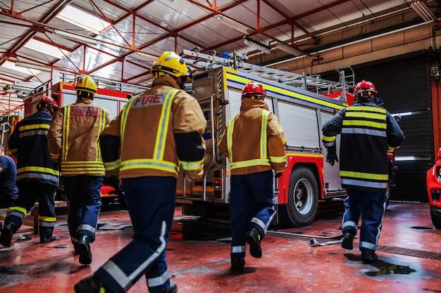 Grupa strażaków w mundurach ochronnych w hełmach biegnących w kierunku wozu strażackiego i pędzących na miejsce wypadku.