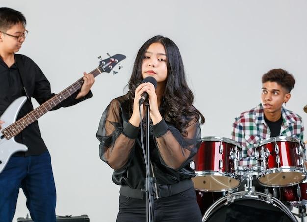 Grupa strzał nastoletnich przyjaciół grających muzykę i śpiewających razem. młodsi uczniowie grają na gitarze elektrycznej, perkusji i klawiszach. młoda piosenkarka śpiewająca piosenkę z muzykiem w tle