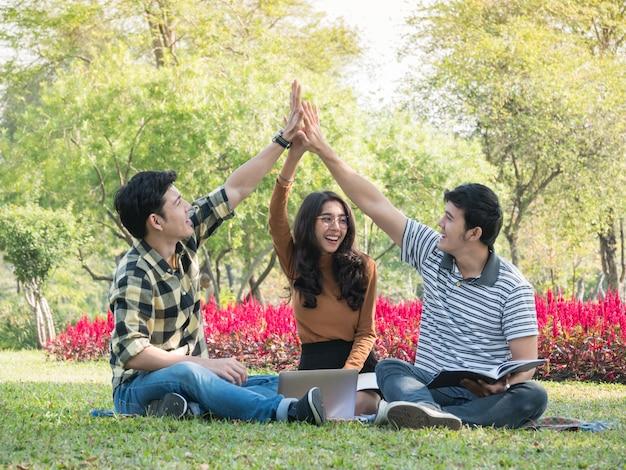 Grupa studenci collegu daje wysokości pięć i ma zabawę wpólnie podczas gdy robić pracie domowej przy parkiem