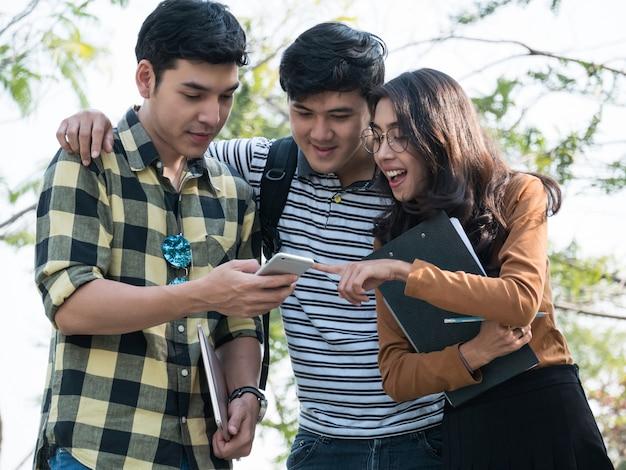 Grupa studenci collegu ogląda coś na smartphone w parku lub kampusie uniwersyteckim