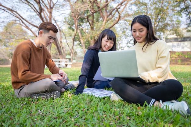 Grupa studenci uniwersytetu azjatykci siedzi na zielonej trawie pracuje i czyta outside wpólnie w parku