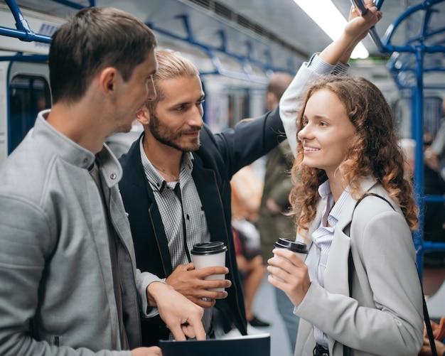 Grupa studentów dyskutujących o czymś w wagonie metra