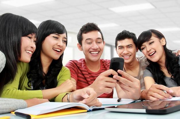 Grupa studentów korzystających z telefonu komórkowego