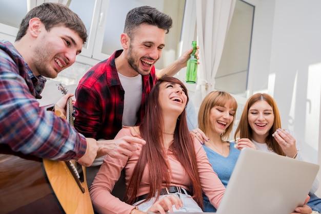 Grupa studentów lub nastolatków z komputerami typu laptop i tablet pc w domu, zabawy