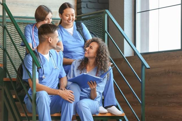 Grupa studentów medycyny na schodach w nowoczesnej klinice