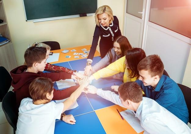 Grupa studentów pracujących jako zespół. kładzenie sobie rąk razem z nauczycielem. praca zespołowa i komunikacja.