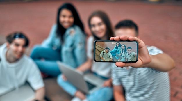 Grupa studentów siedzi na schodach w pobliżu kampusu z laptopami, relaksując się, rozmawiając i robiąc selfie na smartfonie.