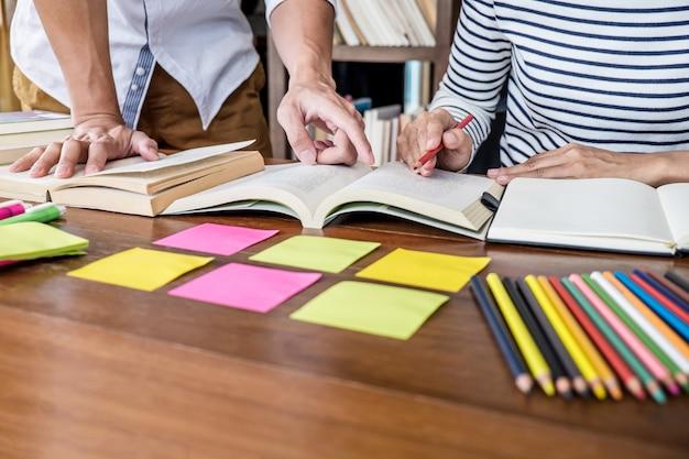 Grupa studentów siedzi przy biurku w bibliotece studiując i czytając, odrabiając lekcje i odrabiając lekcje