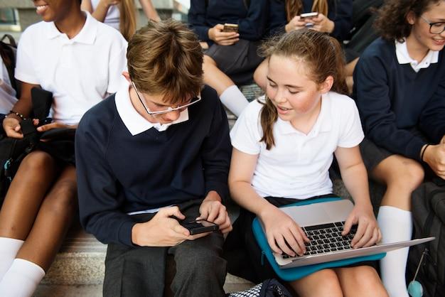 Grupa studentów siedzi przy schodach i za pomocą urządzeń cyfrowych