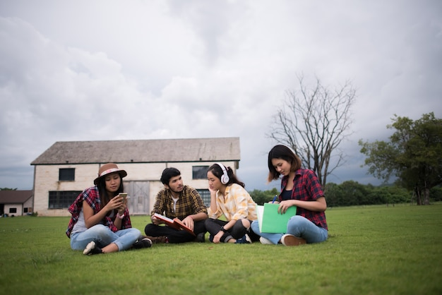 Grupa studentów siedzi w parku po klasie. ciesz się rozmową.