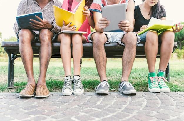 Grupa studentów studiujących na zewnątrz.