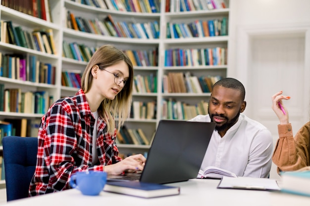 Grupa studentów studiujących w bibliotece uniwersyteckiej lub szkolnej, dziewczynka rasy białej i afrykański chłopiec korzysta z laptopa