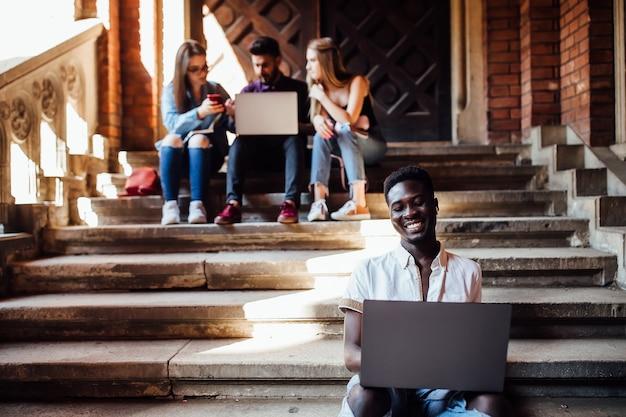 Grupa studentów studiuje w pobliżu uniwersytetu w pobliżu kampusu z laptopami