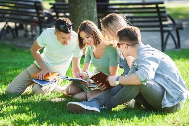 Grupa studentów uczących się lekcji na zewnątrz. uczniowie czytający podręczniki lub samouczek. studiowanie młodzieży w parku.