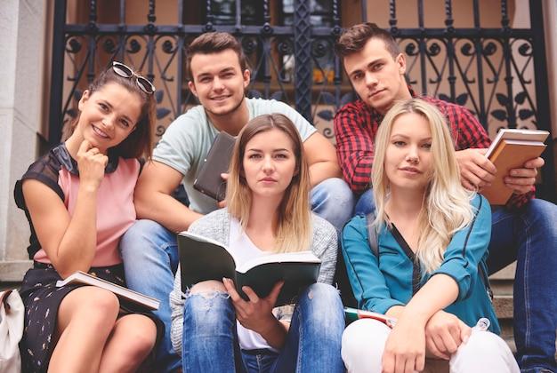 Grupa studentów uczących się na schodach na zewnątrz