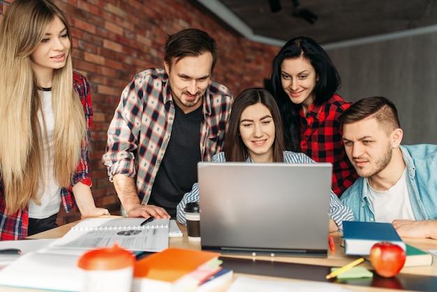 Grupa studentów uczelni wspólnie przygotowuje się do egzaminów. osoby posiadające laptopa przeszukują internet