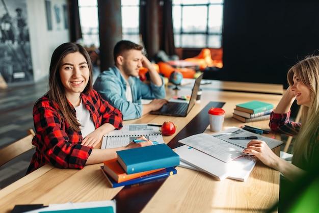 Grupa studentów uniwersytetu siedzi przy stole razem.