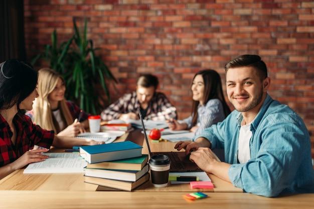 Grupa studentów uniwersytetu siedzi przy stole